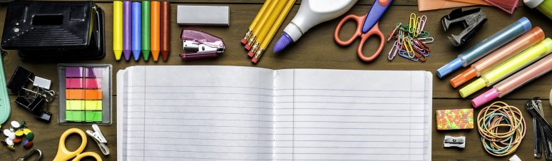 Back to school themes. Overhead shot of stationery on wood desk with paper notepad and frame of school office supplies